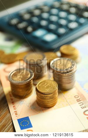 Money concept. Black calculator with banknotes and coins, close up
