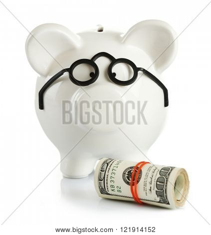 Piggy bank in glasses with rolled dollars isolated on white