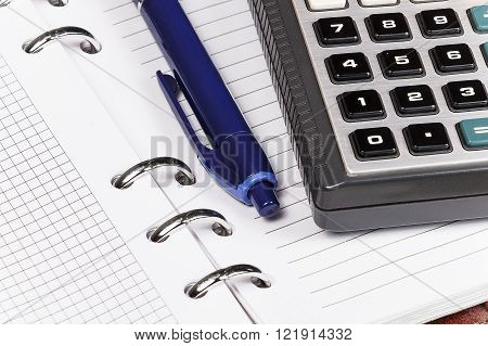 Open notebook on which lies a blue pen and calculator. Sheets of notebook in the box and in the ticker.