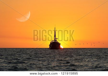 Ship sunset is a silhouette of an old ship with a flock of birds flying by and the moon rising in the sunset sky.