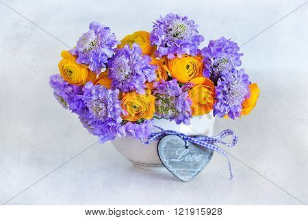 Beautiful bouquet of flowers.Yellow ranunculus flowers and scabious close-up in a vase ,decorated with a wooden heart on the table.