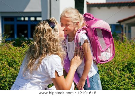Mother taking her daughter to school, saying her goodbye for the day