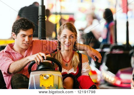 Couple in traditional German or Bavarian costume in a bumper car / dodgem ride