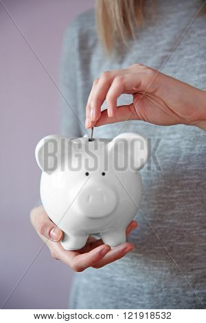 Woman putting coin into white piggy bank