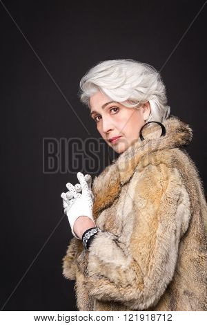 Portrait of beautiful fashion senior rich woman looking at camera. Rich lady in fur coat posing in studio isolated on black background.