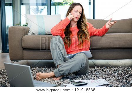 annoyed woman sitting on the ground making a phonecall