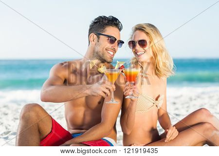 Happy couple sitting back to back drinking cocktail on a sunny day