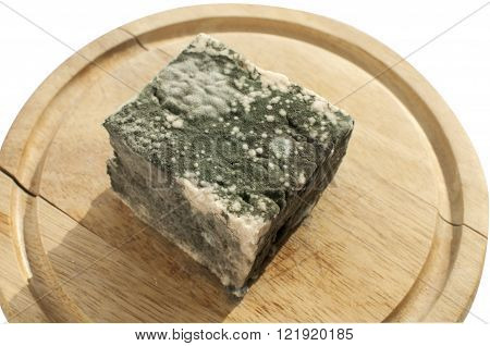 Moldy lump of white cheese on wooden tray isolated on white background