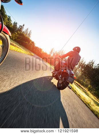 Motorcyclist riding a chopper on a road in morning sun