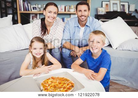 Portrait of smiling family with pizza on table at home