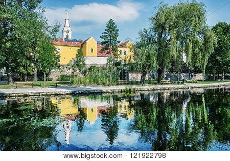 Church and convent in Tapolca is mirroring in the water level of the lake. Hungary central Europe. Architecture and nature.