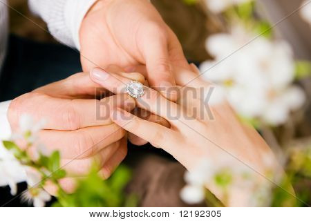 Couple - he is proposing marriage by giving the ring