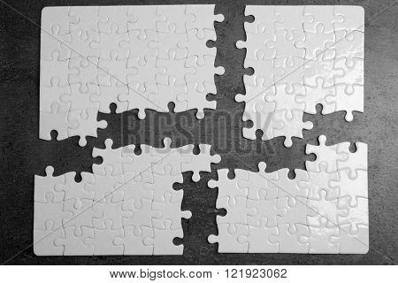 Four parts of white jigsaw puzzle with missing pieces on grey background