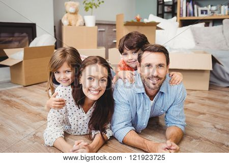 Portrait of happy family lying on hardwood floor at home