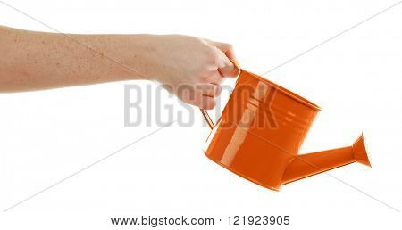 Female hand holding a small orange metallic watering can with spout isolated on white background