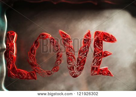 Red quilling word love on a glass