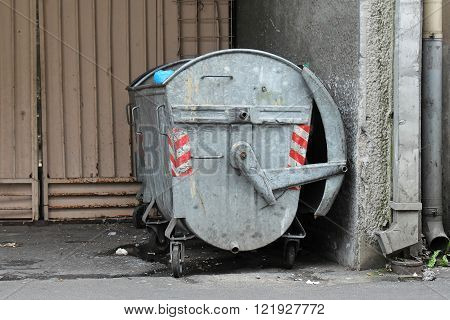 Open metal dumpster in dirty residential area