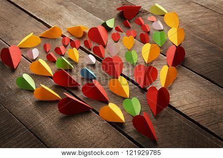 Handmade varicolored paper heart on wooden background