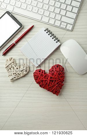 Computer peripherals with wicker hearts, notebook and mobile phone on light wooden table