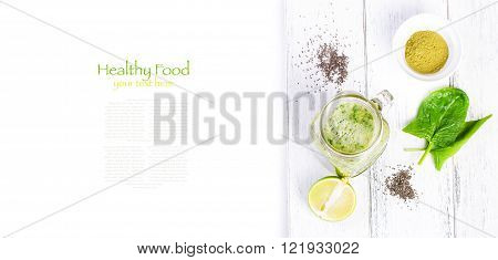 Healthy green smoothie with spinach kiwi banana chia seeds lime and green tea matcha in a glass jar on a white wooden background with copy space top view