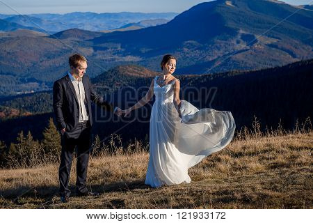 Beautiful bride and handsome groom holding hands on the mountain peak. Honeymoon