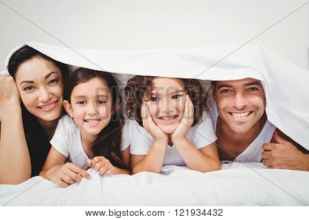 Close-up of cheerful family below blanket on bed at home