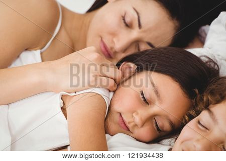 Close-up of children sleeping with mother on bed at home
