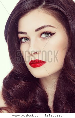 Vintage style close-up portrait of young beautiful woman with winged eyes make-up, red lips and long curly hair