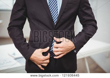 Midsection of businessman adjusting suit while standing in office