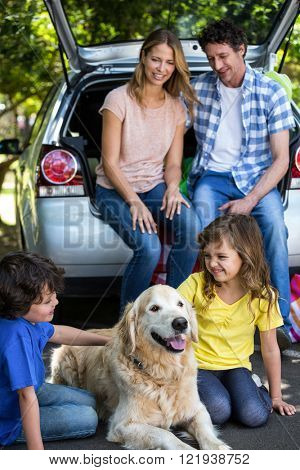 Children ruffling the dogs fur in a park