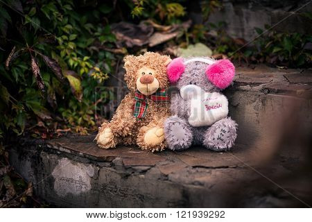 Couple of teddy bears sitting together on the stone stairs. they looks like a couple boy and girl. Teddy bear girl keeps muff with inscription