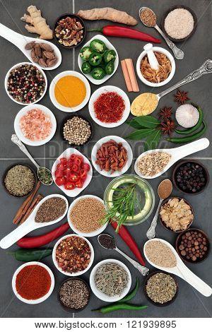 Spice and herb food seasoning sampler over grey slate tile background.