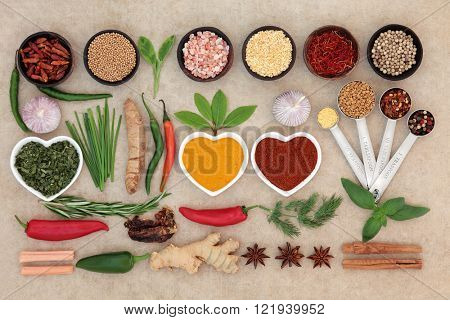 Herb and spice  food abstract selection in bowls and heart shaped china dishes with measuring spoons over natural hemp paper background.