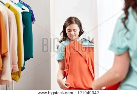 clothing, wardrobe, fashion, style and people concept - happy plus size woman with shirt on hanger at mirror at home