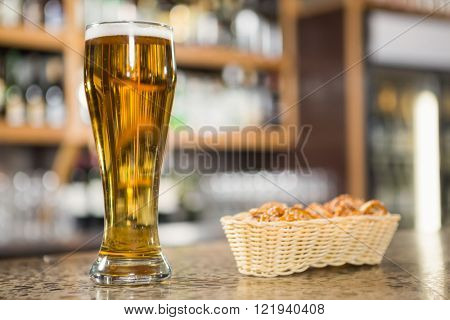 View of a pint of beer and pretzels in a pub