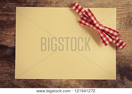 Red cell bow tie on beige paper background