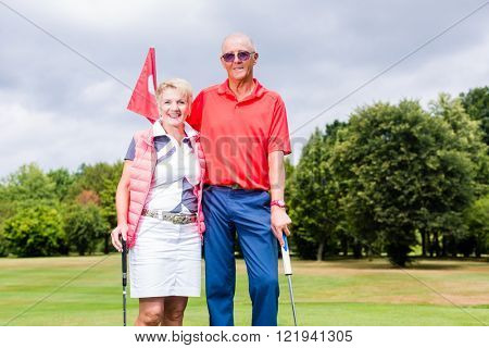 Senior couple playing golf standing on green