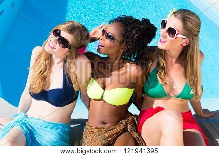 Diversity girls sitting on swimming pool in summer relaxing, African and Caucasian girls