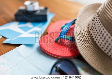 summer vacation, tourism and objects concept - close up of travel map, airplane tickets, flip-flops and hat