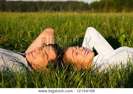 Young couple lying together on a green meadow in summer in the sunshine having eyes closed taking a nap