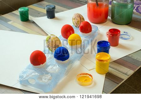 Painted Easter eggs and painting supplies on a wooden table.
