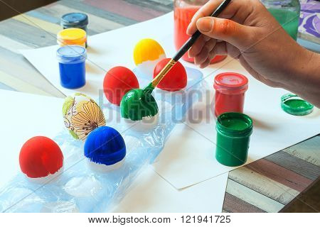 Female hands painting Easter eggs on a wooden table with painting supplies.