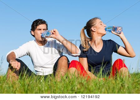 Young sport couple was jogging on a green summer meadow but is resting now, replenishing themselves with a zip of water