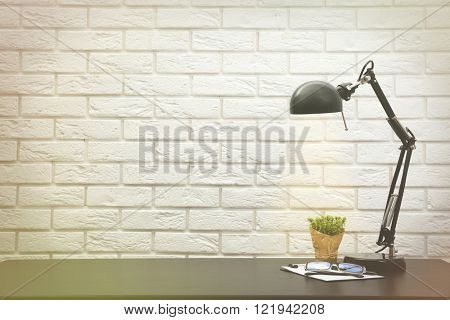 Office lamp on the desk on brick wall background