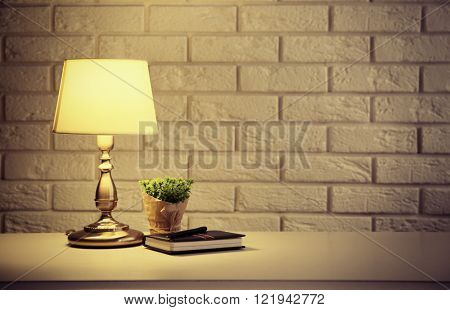 Night lamp on the locker on white brick wall background