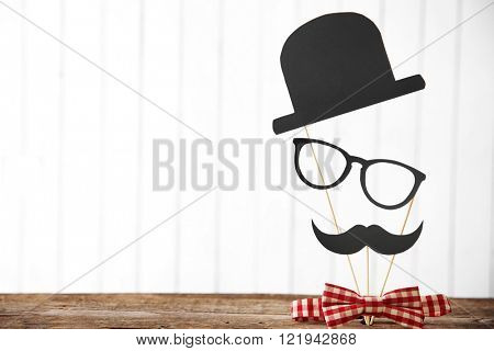 Tie bow with paper mustache, hat and glasses on wooden table