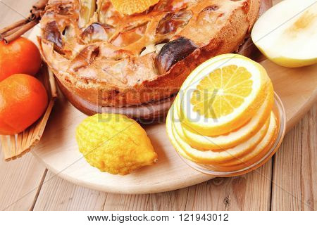 baked food : big apple pie served with fresh apples, raw lemon and mandarin,  tea cup on wooden plate over table