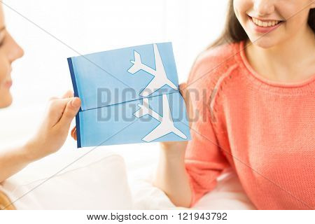 tourism, travel, vacation and people concept - close up of women with airplane tickets at home