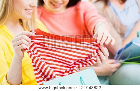 clothing, fashion, style and people concept - close up of happy young women or teenage girls with shopping bag and t-shirt