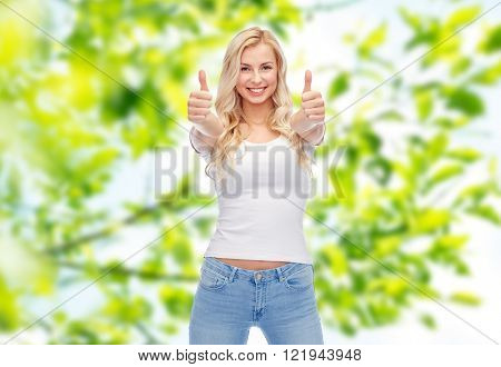 emotions, expressions, advertisement and people concept - happy smiling young woman or teenage girl in white t-shirt showing thumbs up with both hands over green natural background